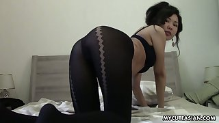 Titless Asian chick takes off pantyhose and plays with shaved pussy